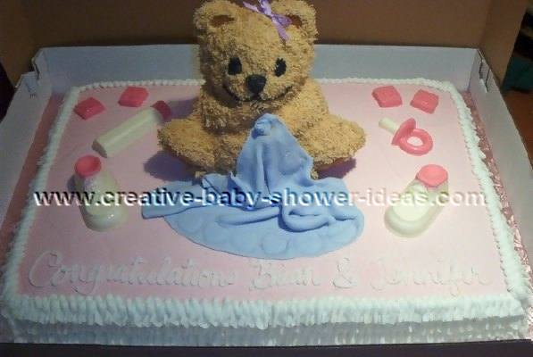 brown teddy bear sitting on pink baby shower cake with blue blanket