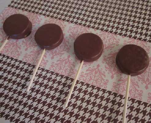 wax paper with white and chocolate covered oreo lollipops sprinkled with colored sprinkles
