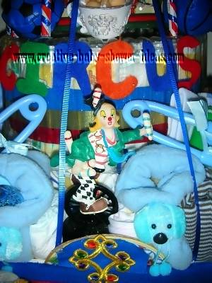 closeup of 1st layer of the circus diaper cake with a plastic clown and plastic safety pins