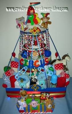 circus carousel diaper cake with ribbons tied to lots of baby supplies and toys