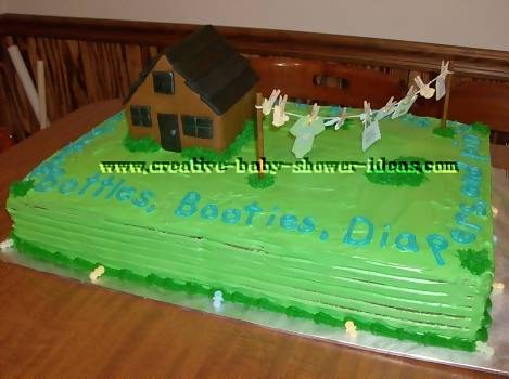 baby clothesline cake next to log house