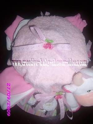 top of cow diaper cake showing pink hat