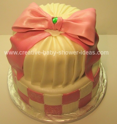 top of pink and white baby shower crown cake showing pink bow and emerald stone