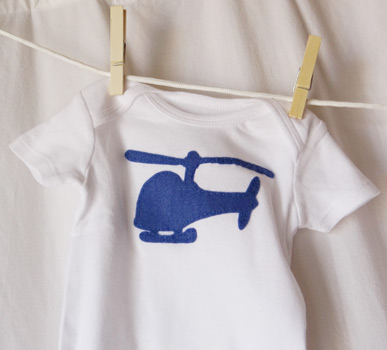 finished blue helicopter onesie hanging on clothesline
