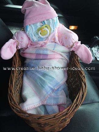 diaper baby in basket wrapped in pink blanket