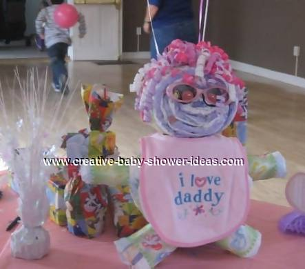diaper baby with pink bib and curling ribbon hair