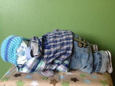 diaper baby in plaid shirt and jeans sleeping on stomach