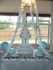baby shower table with six tier blue diaper cake on a cake stand and 2 edible baby bootie cakes