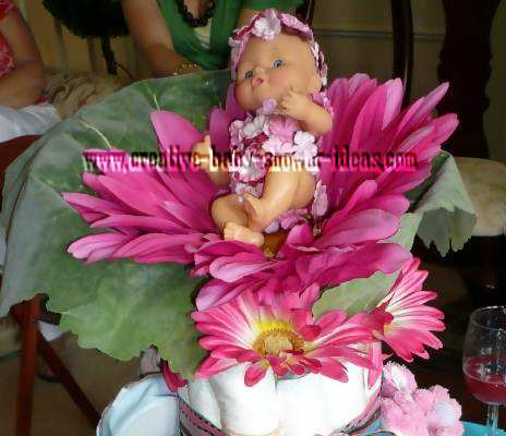 closeup of baby doll on flower diaper cake