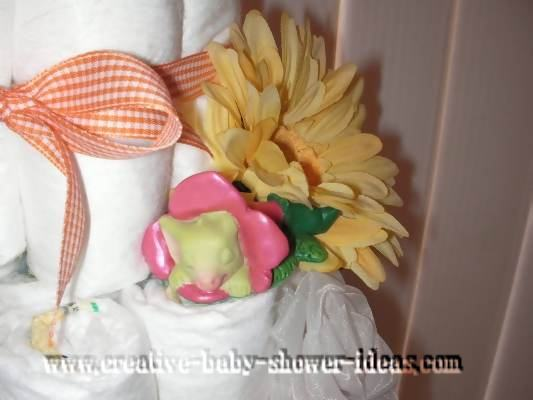 closeup of pocket dragon sleeping on a flower in diaper cake