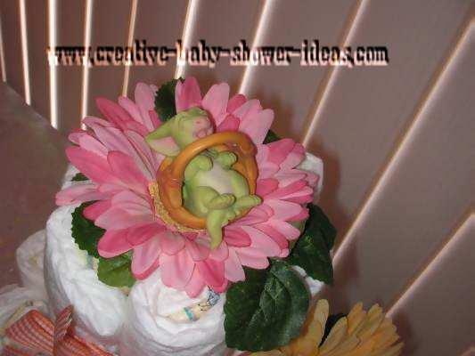 closeup of pocket dragon sleeping on top of diaper cake