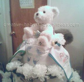 side view of white and blue bear diaper cake