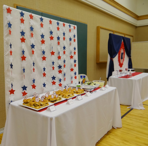 party table with white backdrop and red white and blue garland stars