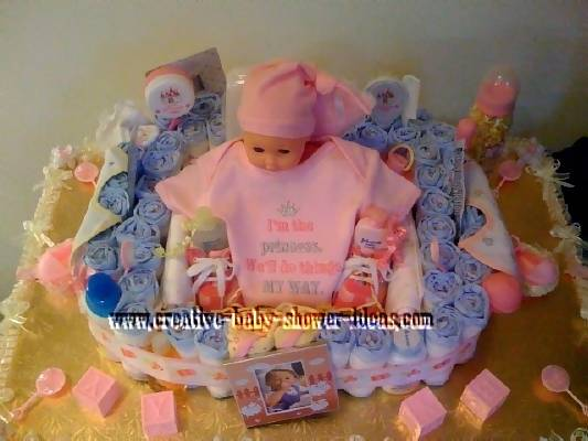 top of baby doll diaper cake showing baby supplies