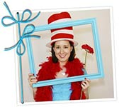 woman smiling for picture at baby shower wearing dr seuss hat holding blue picture frame and red flower