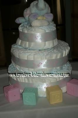 soft white boutique swirl diaper cake with white satin ribbon elephant and baby blocks