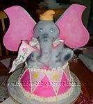 dumbo elephant baby shower cake holding banner and sitting on a drum