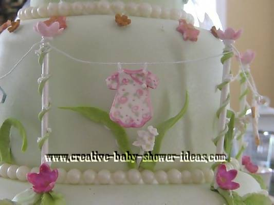 closeup of baby clothes on fairy garden shower cake