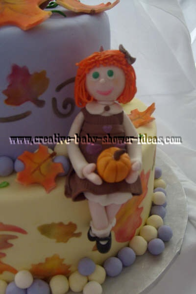 closeup of fall baby shower cake with red headed little girl with brown dress and and pumpkin sitting on cake