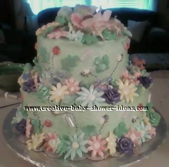 light green cake with lots of pastel flowers and bugs