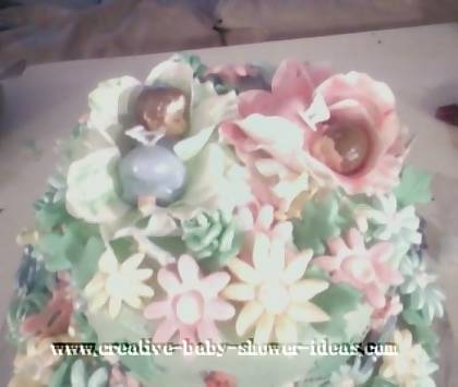 closeup of top of the green cake showing 2 sleeping babies in flowers