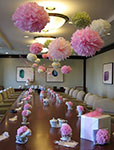 picture of an office baby shower in board room with vintage tea pots and tissue paper flowers and pom poms as decorations