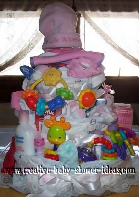 girl diaper cake with lots of baby items and a hat that says little ballerina