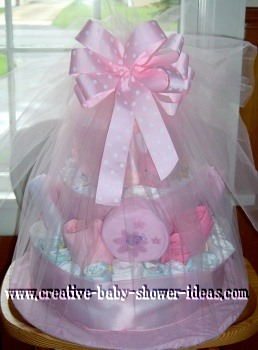 diaper cake with pink satin ribbon around layers and tied with white tulle