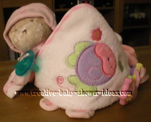 front of pink towel cupcake with teddy bear and pacifier