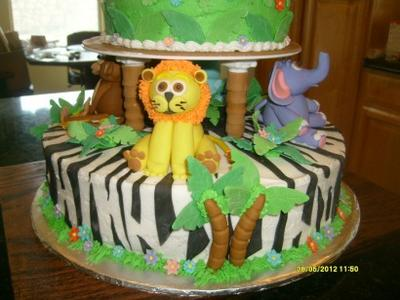 closeup of lion and elephant on white and black zebra stripe cake layer
