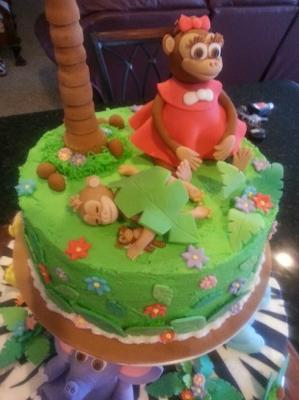 top of jungle cake with sister and baby monkeys on a green grass layer with palm trees