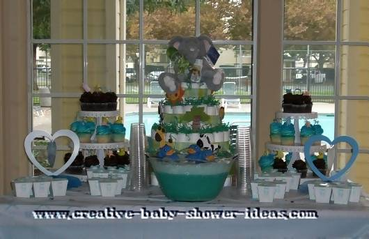 jungle diaper cake on baby shower table with 2 cupcake stands green punch heart decorations and favor boxes