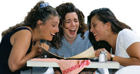3 women laughing really hard at some papers they are looking at