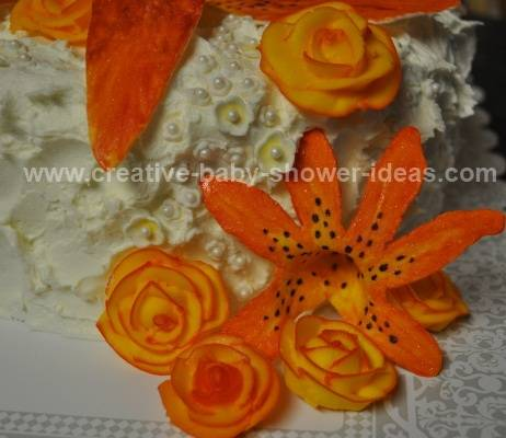 sideview of baby cake showing different orange flowers and edible white pearls