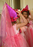 girl in princess costume and hat looking in mirror