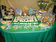 monkey baby shower table display with sheet cake and lots of favors and prizes lined up