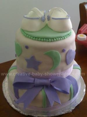 white baby shower cake with green and lavendar moon and stars decorations