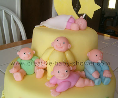 2 tier yellow fondant cake with sleeping babies and moon and stars