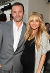 pregnant nicole richie wearing black dress standing next to husband