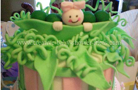 closeup of top of pea in pod cake with smiling baby and pink bow on her head