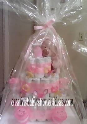 finished pink teddy bear diaper cake wrapped in cellophane