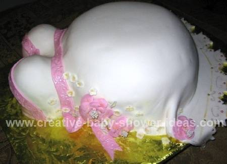 side view of pink and white pregnant belly cake