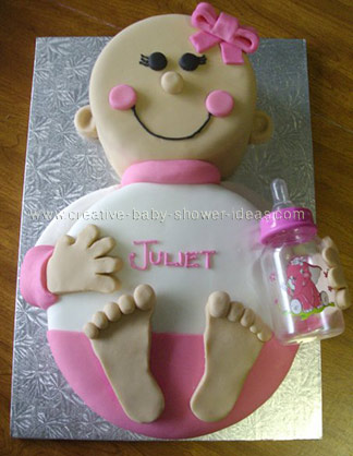 smiling pink girl baby cake wearing white and pink outfit with pink headband
