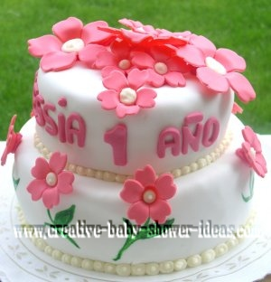white fondant baby cake with cream pearls and bright pink flowers