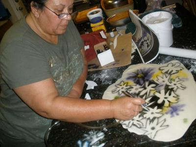 cake decorator making spray on flowers for pregnant belly cake