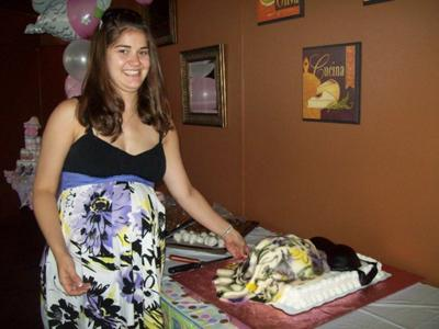 mom to be standing nex to pregnant belly cake