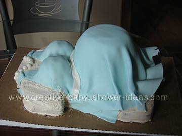 sideview of a pregnant belly cake with blue dress and pearls