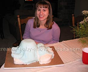 woman sitting next to a blue pregnant belly cake
