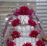 5 tier white princess diaper cake with pink daisies and sheer white ribbon