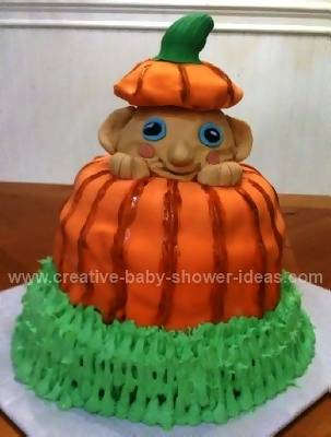 cute baby peeking out from inside pumpkin cake wearing top of pumpkin as a hat